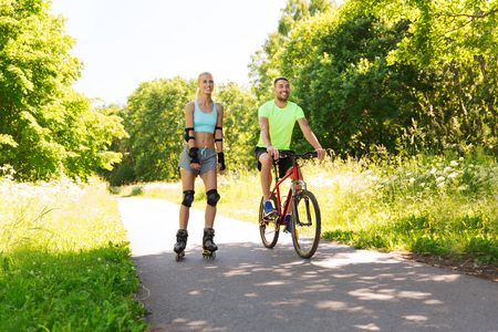 rollerblades: fitness, sport, summer, people and healthy lifestyle concept - happy couple with rollerblades and bicycle riding outdoors at summer