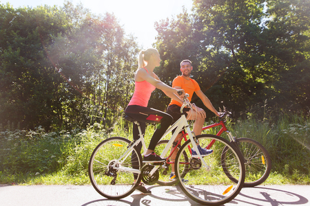 healthy men: fitness, sport, people and healthy lifestyle concept - happy couple riding bicycle outdoors at summer