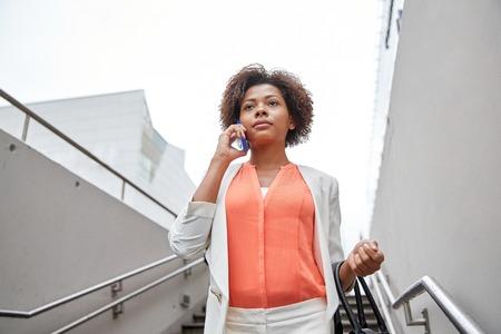 down stairs: negocio, la comunicación, la tecnología y el concepto de la gente - joven africano americano de negocios que invita al teléfono inteligente bajar escaleras en paso subterráneo de la ciudad Foto de archivo