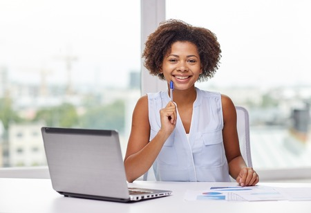 black girl: education, business and technology concept - happy african american businesswoman or student with laptop computer and papers at office