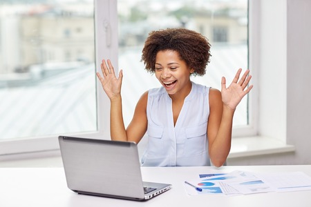 happy african: education, business, success and technology concept - happy african american businesswoman or student with laptop computer and papers at office