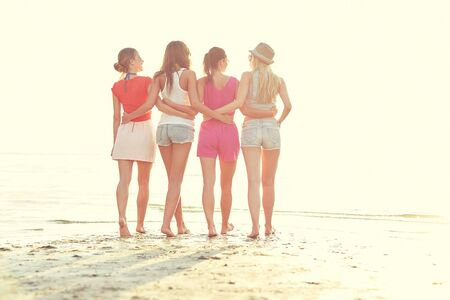 back view: summer vacation, holidays, travel, friendship and people concept - group of young women walking on beach