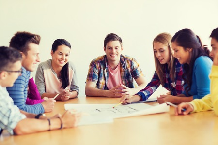 architects: education, school, architecture and people concept - group of smiling students with blueprint meeting indoors Stock Photo