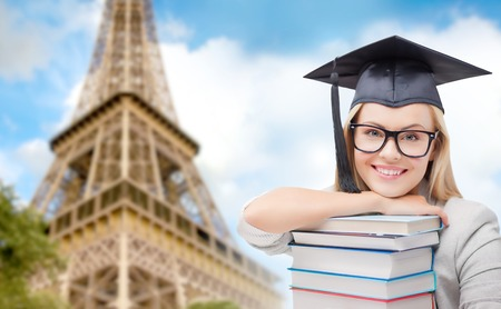 trencher: education, school, knowledge and people concept - picture of happy student girl or woman in trencher cap with stack of books over paris eiffel tower background Stock Photo