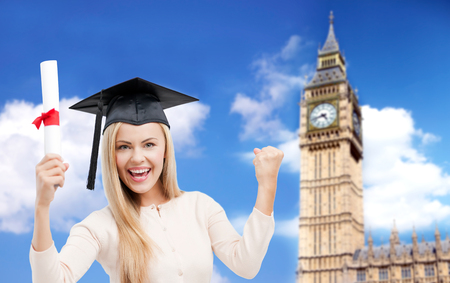 trencher: education, school, knowledge, graduation and people concept - happy student girl or woman in trencher cap with diploma certificate over big ben tower in london background Stock Photo