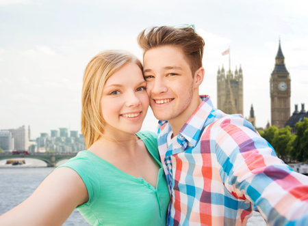 british girl: travel, vacation, technology and friendship concept - happy couple taking selfie over big ben and thames river in london background