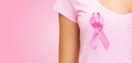 breast cancer awareness ribbon: healthcare, people, charity and medicine concept - close up of woman in t-shirt with breast cancer awareness ribbon over pink background