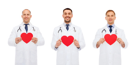 doctors smiling: medicine, profession, cardiology, charity and health care concept - three smiling male doctors with red heart and stethoscope