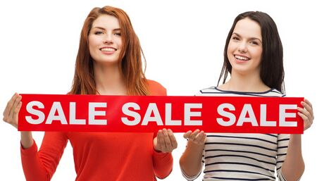 sale sign: shopping, sale, and gift sconcept - two smiling teenage girls with sale sign