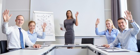 group meeting: business, people and teamwork concept - group of smiling businesspeople meeting and waving hands in office