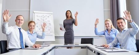 affaires, les gens et concept d'équipe - un groupe de sourire des gens d'affaires et de réunion agitant les mains dans le bureau
