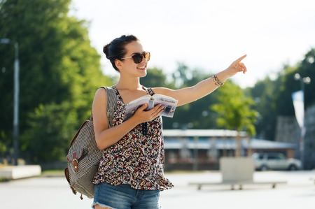 foreign: tourism, travel, summer holidays and people concept - happy teenage girl with guidebook and backpack in city Stock Photo