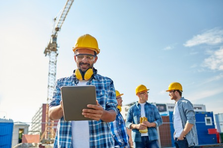 site: business, building, industry, technology and people concept - smiling builder in hardhat with tablet pc computer over group of builders at construction site