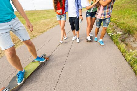 hang body: people, leisure and sport concept - close up of teenage friends with longboards and drinks outdoors