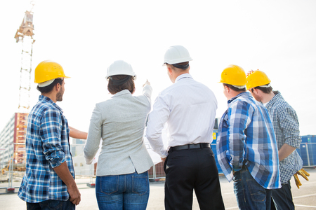 Unternehmen, Gebäude, Teamarbeit und Menschen Konzept - Gruppe von Bauherren und Architekten in Streetware mit Blueprint auf Baustelle