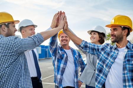 negocio, construcción, asociación, el gesto y la gente concepto - primer plano de la sonrisa constructores y arquitectos en cascos haciendo altos cinco al aire libre