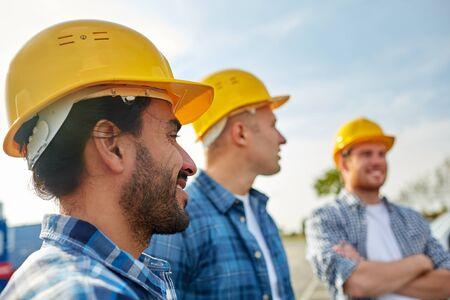 Geschäft, Gebäude, Teamarbeit und Menschen Konzept - Gruppe von Bauherren in Schutzhelmen auf der Baustelle lächelnd Standard-Bild