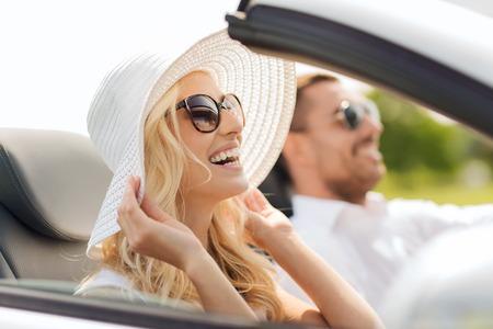 运输,休闲,公路旅行和人概念 - 驾驶在敞蓬车汽车的愉快的男人和妇女户外