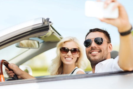 drive car: road trip, leisure, couple, technology and people concept - happy man and woman driving in cabriolet car and taking selfie with smartphone