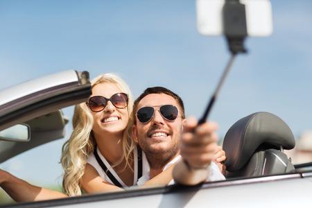 Straße Reise, Freizeit, Paar, Technologie und Menschen Konzept - glücklicher Mann und Frau in Cabrio Auto fahren und mit dem Smartphone auf selfie-Stick, die Foto Standard-Bild