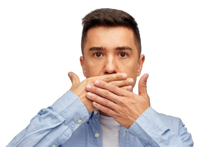 voiceless: problem, emotion, sorrow and people concept - face of middle aged latin man covering his mouth with hand palm