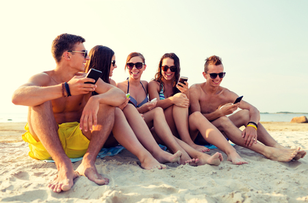 cell phone: friendship, leisure, summer, technology and people concept - friends with smartphones sitting on sandy beach