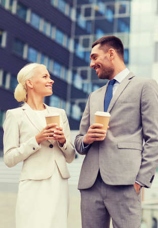 personas de pie: business, partnership, hot drinks and people concept - smiling businessmen with paper cups standing over office building