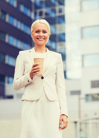 hot secretary: business, hot drinks and people and concept - young smiling businesswoman with paper coffee cup over office building
