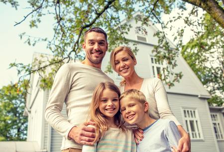 Familie, Glück, Generation, Haus und Menschen Konzept - glückliche Familie vor dem Haus stand im Freien Standard-Bild