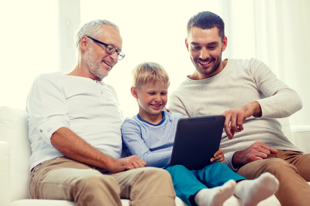 computer generation: family, generation, technology and people concept - smiling father, son and grandfather sitting on couch with tablet pc computer at home