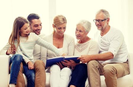 familia, la felicidad, la generación y la gente concepto - familia feliz con el libro o álbum de fotos sentado en el sofá en casa