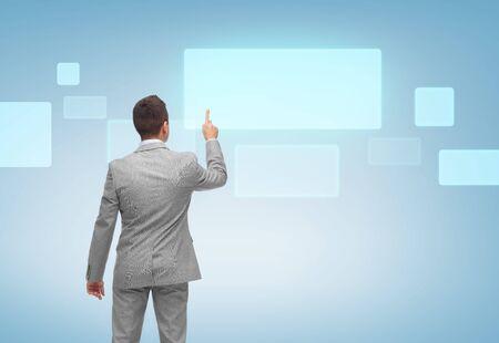 negocio, la gente, la publicidad y la tecnología concepto - hombre de negocios que señala el dedo o tocar la pantalla virtual en blanco sobre fondo azul de la parte posterior