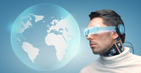 technological and communication: people, technology, future and progress - man with futuristic glasses and microchip implant or sensors over blue background and earth globe hologram Stock Photo