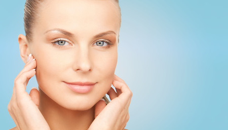 touching face: beauty, people and body care concept - beautiful young woman touching her face over blue background Stock Photo