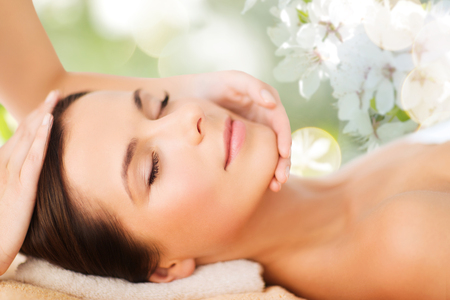 spa, beauty, people and body care concept - beautiful woman getting face treatment over green natural background