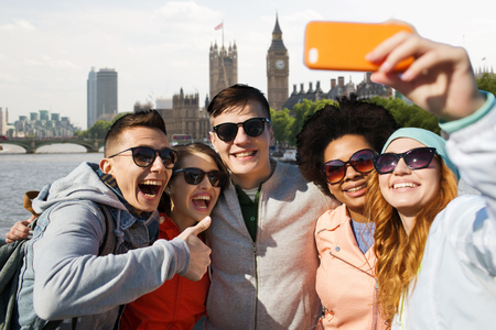 britain: tourism, travel, people, leisure and technology concept - group of smiling teenage friends taking selfie with smartphone over houses of parliament and thames river in london background Stock Photo