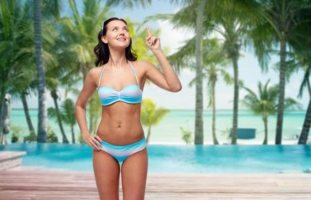 d0bdbdd2889 #57275912 - 人々、旅行、水着、夏のコンセプト - ヤシの木とプール ホテル リゾートの背景で熱帯のビーチを架空の何かまでビキニ水着人差し指 で幸せな若い女