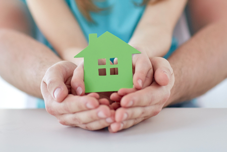 hand holding house: people, charity, family, real estate and home concept - close up of man and girl holding green paper house cutout in cupped hands