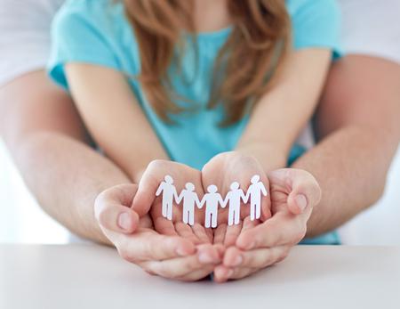 demografia: la gente, la caridad, la demografía y la pareja del concepto - cerca del padre y la niña con el recorte humana en las manos ahuecadas en el hogar