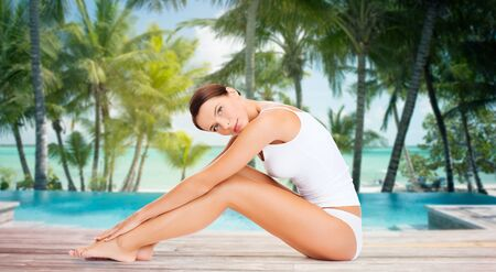 people, beauty, spa, travel and resort concept - beautiful woman in cotton underwear touching her legs over swimming pool on beach with palms background Stock Photo - 57275924