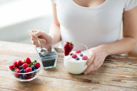 gesunde Ernährung, vegetarische Kost, Diät und Menschen Konzept - Nahaufnahme von Frau Hände mit Joghurt, Beeren und Mohn oder Chiasamen auf Löffel