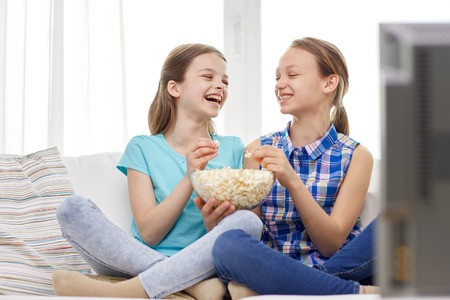friends eating: people, children, friends and friendship concept - two happy little girls watching tv, laughing and eating popcorn at home