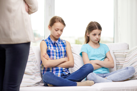 regretful: people, children, misbehavior, friends and friendship concept - upset feeling guilty or displeased little girls sitting on sofa and mother at home