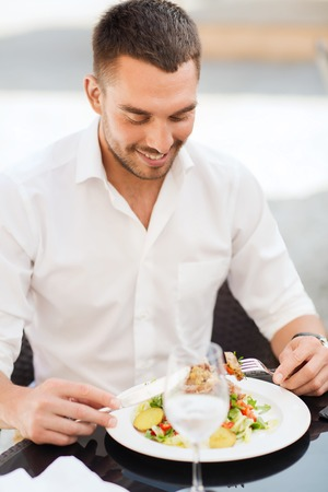 eating dinner: people, holidays, food and leisure concept - happy man with fork and knife eating salad for dinner at restaurant terrace