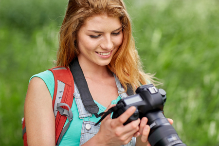 travel woman: adventure, travel, tourism, hike and people concept - happy young woman with backpack and camera photographing outdoors Stock Photo