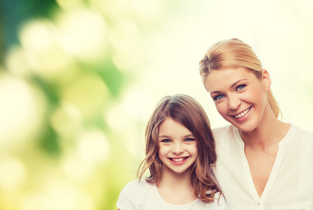 beautiful preteen girl: family, childhood, happiness, ecology and people - smiling mother and little girl over green background