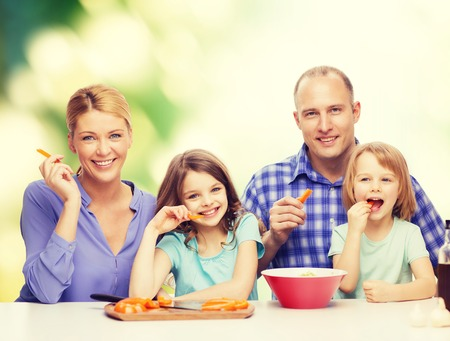 eating dinner: food, family, children, hapiness and people concept - happy family with two kids eating at home