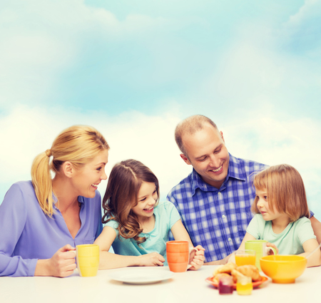 sky brunch: food, family, children, hapiness and people concept - happy family with two kids having breakfast at home