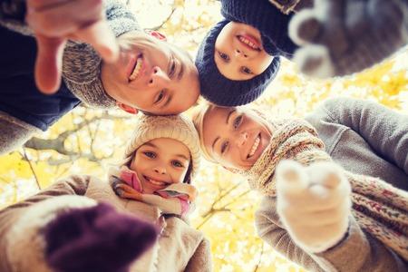 caes: la familia, la infancia, la temporada, el gesto y concepto de la gente - familia feliz que señala el dedo en usted en parque del otoño Foto de archivo