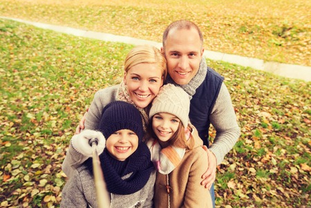 pictures: family, childhood, season, technology and people concept - happy family photographing with selfie stick in autumn park